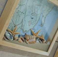 Map in shadow box with shells and sand