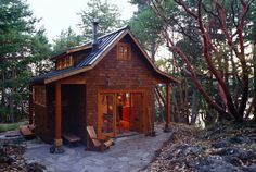 This 400-square-foot cabin with a refined decor sits nestled among fir, cedar, and madrone trees on the East Sound of Washington state's Orcas Island. Designed by architect David Vandervort, the cross-shaped floorplan creates distinct alcoves for the kitchen, dining room, and bathroom, while a ladder provides access to the loft bedroom above the central living room. French doors lead out to a patio of flagstone, which is also used at the cabin's entrance. (Building plans of a prototype of this c