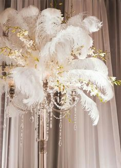 Glam Feathers To heighten the drama, tall arrangements of feathers lend an air of old Hollywood glamour. Imagine women in elbow length gloves, sipping champagne beneath towering vases of white ostrich feathers – how chic