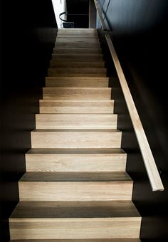 Wooden stairs with black walls.