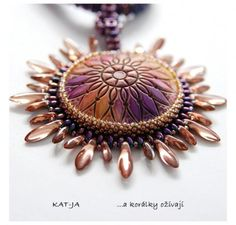 A beautiful blend of patterns between the domed disk and the beaded bezel. The domed disk was provided by Ivabro - Iva Brozova. The finished piece is by Katka Václavíková, working as Kat-ja. Get the details on The Polymer Arts Blog, http://www.thepolymerarts.com/blog/10043
