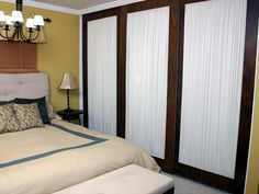 See past boring closet doors to the fresh, clean canvases crying out for decoration. For this bedroom makeover, old mirror doors were turned around and fabric was added to the backs for a soft, stylish alternative. You could also transform surfaces like this with modern artwork.