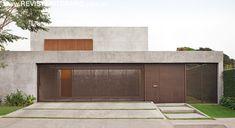 O fulget reveste a fachada e emoldura o portão frontal, executado com vergalhões de obra na forma de painéis. A composição marca os materiais essenciais do projeto: cimento, aço e madeira