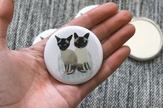 Pocket mirror designed by Nicola Rowlands. Features two cats to watch over you and tell you when you have an eyebrow hair thats gone wonky. 58mm (2 1/4 inch) pocket mirror in brilliant full colour on one side and mirror glass on the other.  Check out my other mirrors too