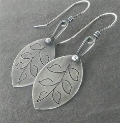 This pair of earrings is handmade by me using sterling silver. They measure 2 1/8 inches in length from the top of the ear wire to the bottom of the leaf dangle. They have been oxidized to show detail and add rustic charm.