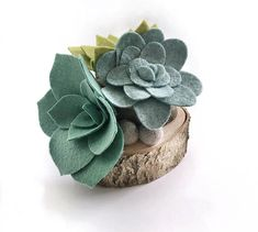 Felt Succulent Arrangement | Made of soft and durable wool blend felt on a sturdy wood base. This felt succulent arrangement features succulents in shades of green with felt ball accents on a two-tiered cut wood base. Dimensions: 4.5 L x 4.5 W x 5 H Would be the perfect addition to a