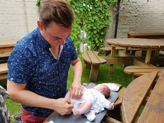 Beer garden picnic tables make perfect baby change units. A picture of a father that is changing baby's nappies in the garden, on a garden table