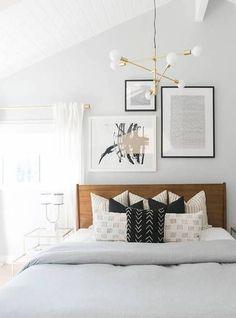 Modern guest room decor with brass light fixture and wooden headboard