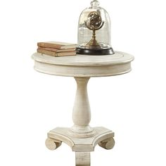 Stage a family of framed photos or a country-chic vignette atop this stylish end table, featuring a pedestal base, distressed white finish, and scroll feet.
