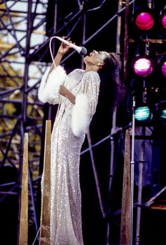 The 25 Best Tour Costumes of All Time | Diana Ross wearing a feather-trimmed silver beaded gown on stage in 1983