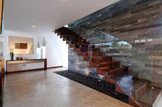 Escada toda revestida com madeira, fazendo contraste com o revestimento de pedras do fundo. O guarda-corpo de vidro deixa a vista livre e não polui o visual já trabalhado com outros materiais.