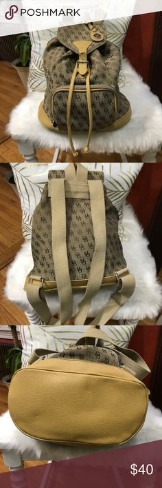 Dooney & Bourke tan and brown backpack Excellent condition, except for buckle strap (see last photo). Still buckles but should be repaired. Smoke Free/Pet Free. Adjustable straps. Interior wall zippered pocket.  Offers Are Welcomed. All Sales Are Final. Dooney & Bourke Bags Backpacks