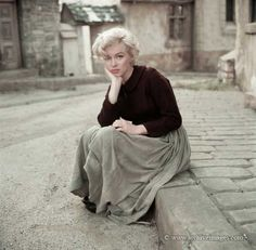 Marilyn Monroe sitting on a curb wearing a peasant dress looking sad taken by Milton H Greene in 1954  (P-89)