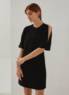 Vestido negro en un ligero y suave tejido fluido con un sutil corte evasé por encima de la rodilla. Escote caja, manga corta amplia con ligeras aberturas en los hombros y dos bolsillos laterales de ojal.