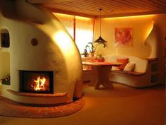 Dining area of a cob home. Beautiful fireplace.