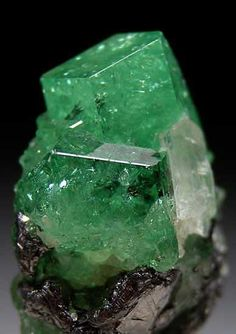 Tsavorite on graphite, with a yellow tanzanite crystal on the right. Tsavorite is a variety of the grossular garnet species. From the Merelani Hills, Tanzania.