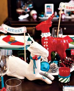 Mod Paper Mache Reindeer Christmas Holiday DIY. Update craft store paper mache deer with spray paint, simple trim, and paper cuffs. Easily customizable to any decor but I love the white, blue, red, & green theme. From Hostess with the Mostess.