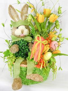 "A cute little bunny with a boxwood belly in this Easter arrangement. Filled with bright yellow tulips and orange hydrangeas, eggs, and trailing green senecio succulents. Measures 27""H X 19""W."