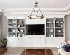 Well appointed features a white built in shelving unit fitted to gray walls featuring gray open shelves with charcoal gray backs lit by Boston Functional Library Wall Lights flanking a mounted flat panel television positioned over white shaker cabinets accented with satin nickel pulls.