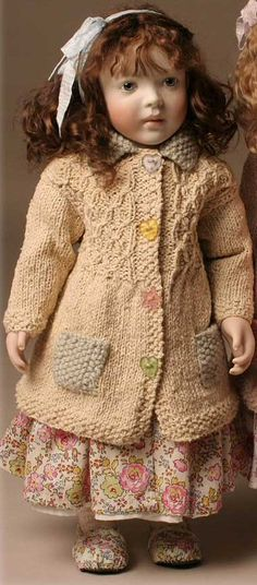 I think this doll is by Lynne and Michael Roche. She's made from wood!