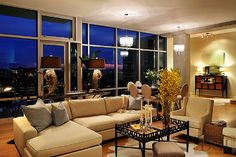 The warmth and brightness of this open living space carry on through the night with light neutral fabrics, elegant accessories, and plenty of fabulous lighting. Nashville penthouse design by Dana Goodman Interiors. www.DanaGoodmanInteriors.com