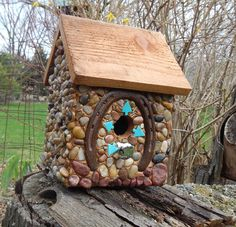 """Horseshoe Birdhouse for sale available at http://www.stonedbirdhouse.com/  Cedar birdhouse with stones and river rock collected from the shores of Lake Michigan, local rivers and from creek beds.  Iron horseshoe and recycled embellishments of art beads enhance the theme. Suitable for outdoor or indoor décor.   7"""" wide X 9 1/2"""" high X 7 3/4"""" deep       1 1/4"""" opening"""
