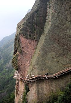 Daredevil workers in Pingjiang, Hunan province, China, risk their lives building a footpath on a sheer cliff face