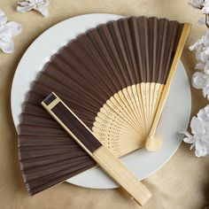 Asian Silk Folding Fans - Chocolate | eFavorMart / Add a classical Asian touch to your wedding, or a special event by presenting your esteemed guests with this special souvenir. Our stylish silk wedding hand fan is intricately handcrafted with a bamboo structure. The framing and spines are crafted from hand-picked bamboo and durably glued with a seamless cut piece of silk to fashion this immaculate magnum opus. Give these swish fans to your respected guests and let them create the lasting…