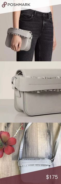 All Saints Maya Gray Leather Convertible Clutch Make a statement on nights out with the Maya Clutch, crafted from luxuriously smooth cow leather with a lamb leather frill detail on the handle. Named after the star of our Spring 17 film, Maya Hawke, this compact bag features a detachable snake chain so you can wear it as a shoulder bag too. Top handle with leather frill detail Folded flap with magnetic closure Internal zip pocket Cotton lining VERY faint mark on back as shown in photos…