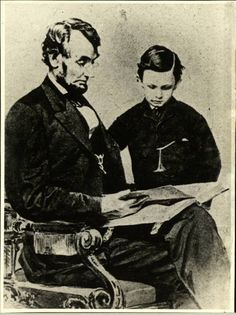 """""""An 1864 Mathew Brady photo depicts President Lincoln reading a book with his youngest son, Tad"""""""
