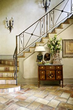 The foyer in interior designer Kim Brockinton's home features antique iron railings, terra cotta tiles salvaged from a barn in France and a Louis XVI-style chest.