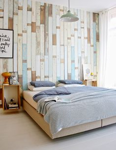 Move beyond just paint. Create an accent wall that offers texture and depth to your room by using upcycled wood. Make a plain wall a masterpiece by running planks vertically and elongating your bedroom backdrop. The idea of a wooden wall replaces the standard notion of artwork and adds beautiful color to this chic Scandinavian inspired space. Want to see other inspiration? Get ideas here.
