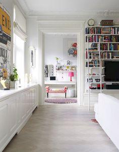 Swedish living room: white built-in cabinet; white shelves; floors; doorway trim + molding; sofa; artwork; colorful room in distance