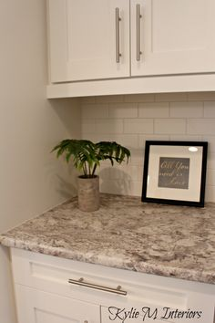 arborite typhoon bordeaux creme laminate countertop with white cabinets, subway tile backsplash and sherwin williams oyster white paint