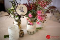 bird inspired table names surrounded by native rustic flowers in wrapped vases