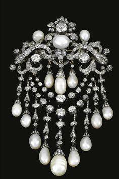 c. 1850 PEARLANDDIAMONDDEVANTDECORSAGE.  Designedas a cartouche of entwined ribbonsandfoliatemotifssetthroughoutwithcushion-shapeddiamondsanddecoratedwiththreepearls,supportinganelaborateswagofpearlanddiamonddropsand diamondchains,mountedinsilverandgold.