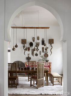 In the dining room of writer and human-rights specialist Maryam Montague's Marrakech, Morocco home, a collection of African masks hangs on the wall with a pair of horn sconces. The space's custom-made dining chairs are inspired by Charles Rennie Mackintosh and Frank Lloyd Wright, and the Berber rug is vintage.   - ELLEDecor.com