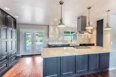 Contemporary kitchen with dark blue cabinets, white zeus quartz countertops and chrome pendant lights