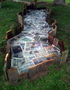 Reclaimed wood garden bed lined with newspapers. Fluid designs.