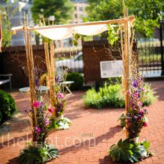 Pink and purple flowers, curly willow and lots of greenery were arranged at each corner of the organic huppah, blending in with the garden-style of the courtyard.