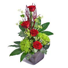 Arrangement with roses in a slate vase. Stylish and modern arrangement with roses, shamrock and exotic foliage