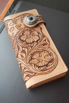 The long leather wallet is made of a genuine leather of a vegetable tanning with a stamping (carving) of a flower pattern of sheridan style. It is
