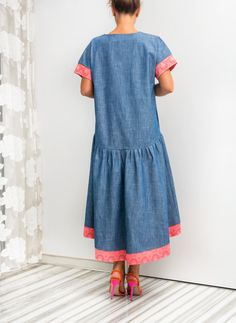 Are you looking for a unique way to stand out this summer? This Denim Maxi Dress is eye-catching and youthful! The asymmetrical line provides a modern twist on a classic denim ensemble, while the drop waist adds a vintage touch. Handmade from high quality denim, this short-sleeved dress is the perfect way to turn heads this summer while staying comfortable.  With the paisley coral hem that just brushes the shins, this versatile summer dress is perfect for a casual night in, a formal garden…