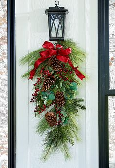 Tuck pinecones into lush greenery like eucalyptus and evergreen branches for a DIY holiday door decoration that adds major holiday curb appeal to your front porch. Best Outdoor Christmas Decorations, Holiday Door Decorations, Coastal Christmas Decor, Pine Cone Decorations, Christmas Centerpieces, Holiday Wreaths, Traditional Christmas Decor, Christmas Front Doors, Christmas Swags