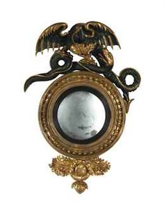 A REGENCY GILTWOOD, BRONZED AND EBONIZED CONVEX MIRROR,  CIRCA 1815  40in. (101.5cm.) high, 27½in. (70cm.) wide