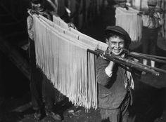 IlPost - Stendere la pasta - Alcuni ragazzi trasportano delle canne su cui è stesa della pasta lunga da far essiccare, in un pastificio di Napoli, nel 1929 (Fox Photos/Getty Images)