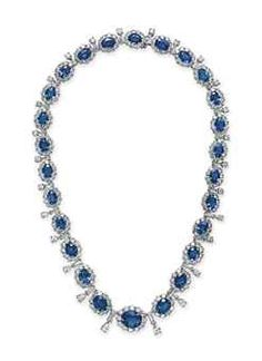 A SAPPHIRE AND DIAMOND NECKLACE   Designed as a graduated series of oval-cut sapphires, each within a circular-cut diamond surround, spaced by tapered baguette, pear and circular-cut diamond links, mounted in platinum, 16 ins. Sold for $56,250.