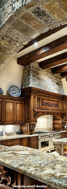 Mediterranean style kitchen.  Love the warm wood and stone together.