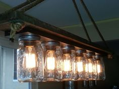 Awesome Image of Hanging Mason Jar Lights. To create your own candle holder, all you will need is a jar or some smaller glasses. Each mason jar is full of a cheesecloth-like material and a stri. Hanging Mason Jar Lights, Mason Jar Chandelier, Mason Jar Lighting, Diy Hanging, Table Lighting, Mason Jar Light Fixture, Lighting Ideas, Diy Chandelier, Light Table