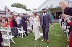 A happy couple high five guests as they recess down the aisle after getting married on the back porch of the Lareau Farm Inn.